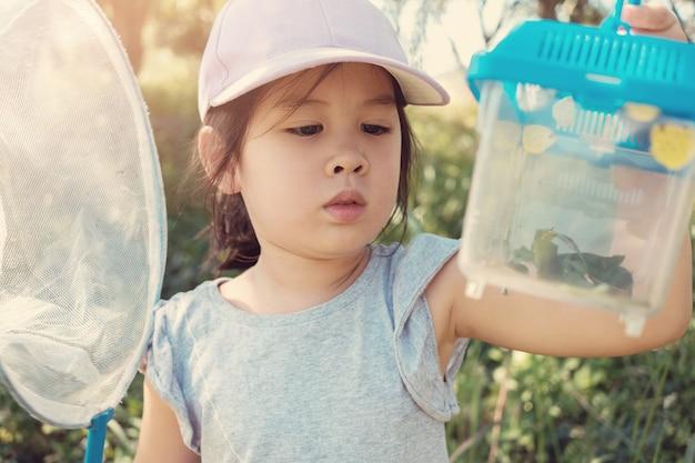 Asain menina assistindo butterfies em uma caixa, educação homeschooling