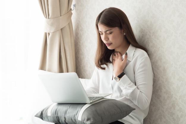 Asain mulher se sentindo mal durante o trabalho, ela está com dor de garganta.