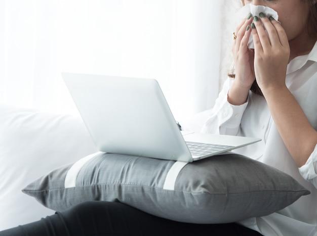 Asain mulher tem febre, ela espirra durante o uso de laptop no quarto.