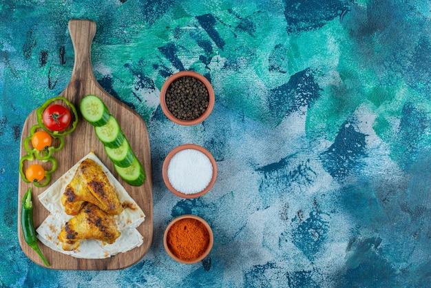 Asas cozidas, lavash e vegetais em uma tábua de corte na superfície azul