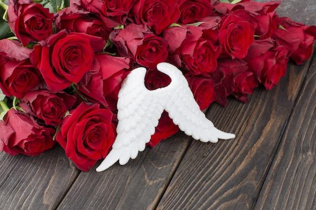 Asas de anjo branco e um buquê de rosas vermelhas