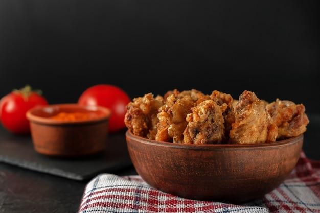 Asas de buffolo recém-cozidas em close-up de tigela de cerâmica com molho de tomate e tomates
