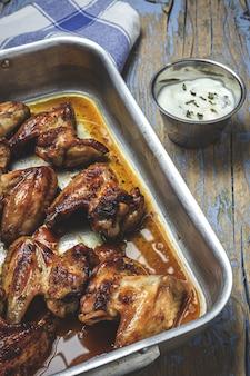 Asas de frango assadas caseiras na assadeira na mesa de madeira