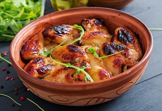 Asas de frango assadas na tigela na mesa de madeira.