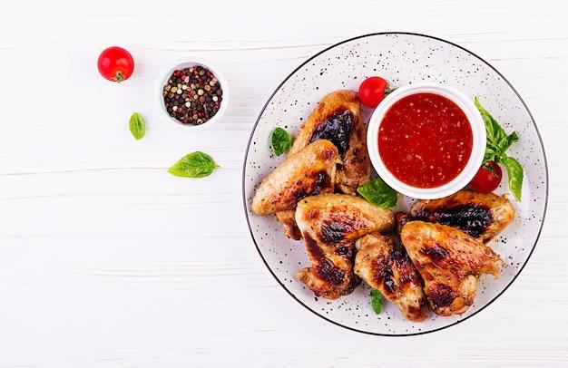 Asas de frango assadas no estilo asiático e molho de tomate no prato