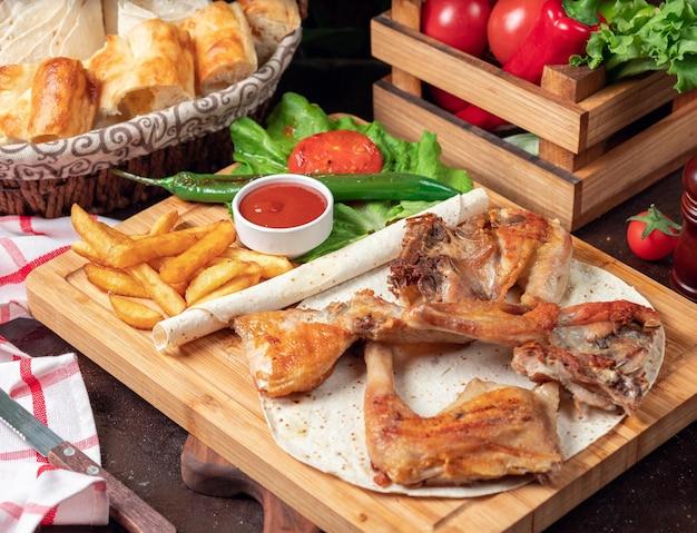 Asas de frango assado com batatas fritas em panela com legumes e ketchup na placa de madeira