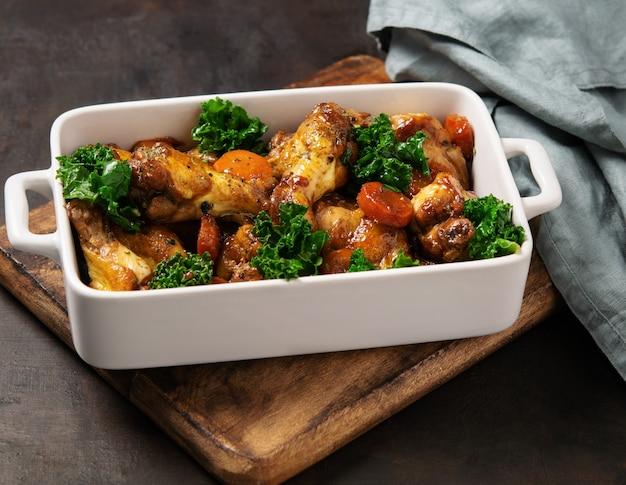 Asas de frango assado com cenoura, couve, alho e molho.