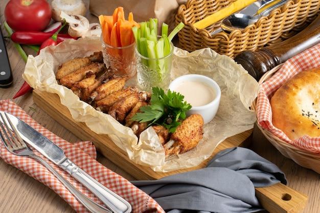Asas de frango assado com molho de queijo e vegetais em uma tábua de madeira