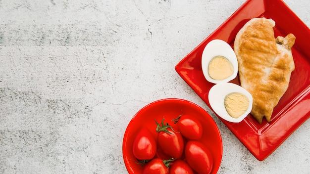 Asas de frango assado com ovo cozido e tomate no fundo áspero