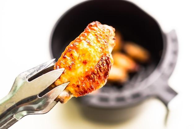 Asas de frango assado com pinças no blur asas de frango assado na fritadeira air no fundo da mesa branca. cozinhar para baixo peso de controle de gordura. alimento para o conceito de saúde.