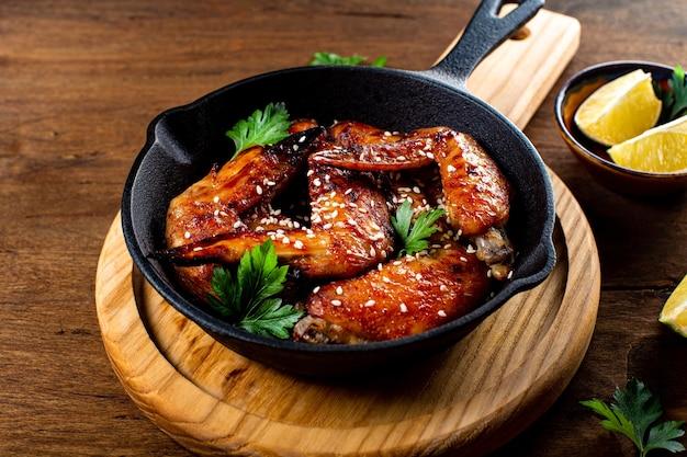 Asas de frango assado com sementes de gergelim, salsa e limão em uma panela preta e mesa de madeira.