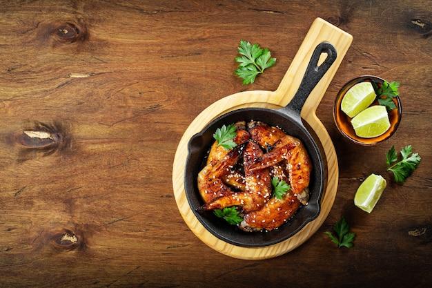 Asas de frango assado com sementes de gergelim, salsa e limão em uma panela preta e vista superior da mesa de madeira.