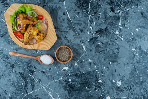 Asas de frango assado e legumes em uma placa de madeira, sobre o fundo azul.