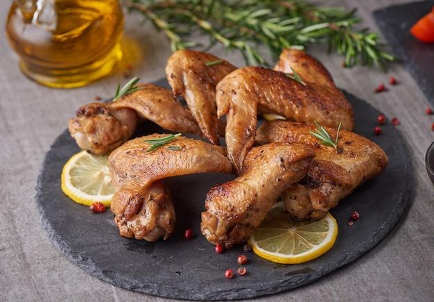 Asas de frango assado em molho barbecue com sementes de pimenta alecrim, sal em uma placa de pedra preta sobre uma mesa de pedra cinza. vista superior com espaço de cópia.