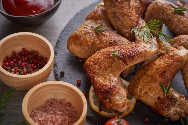 Asas de frango assado em molho barbecue com sementes de pimenta alecrim, sal em uma placa de pedra preta sobre uma mesa de pedra cinza.