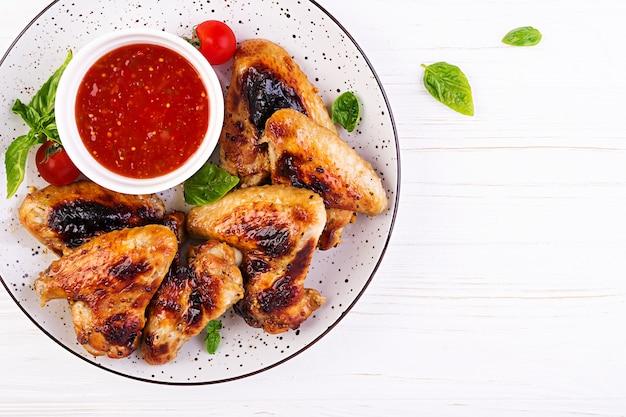 Asas de frango assado no estilo asiático e molho de tomate no prato, vista superior