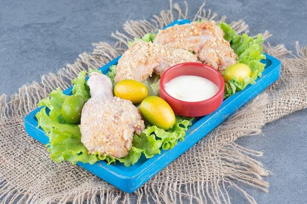 Asas de frango com migalhas de pão e legumes na placa azul.