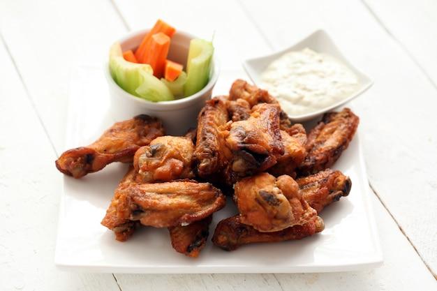 Asas de frango com molho e legumes