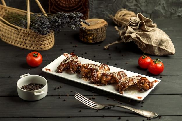 Asas de frango cozidas em molho teriyaki, guarnecido com gergelim