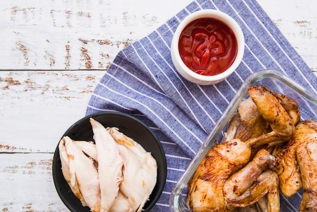 Asas de frango cozido e assado com molho de tomate sobre o guardanapo azul contra a mesa de madeira