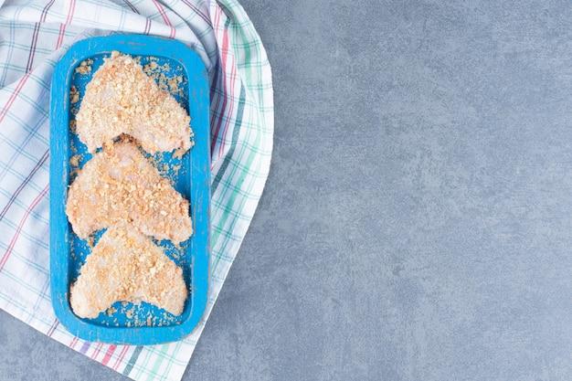 Asas de frango cru com migalhas de pão na placa azul.