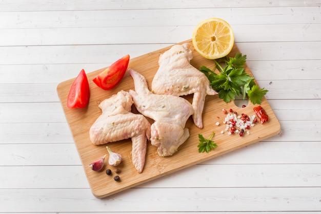 Asas de frango cru com pimenta e verduras no carrinho de madeira