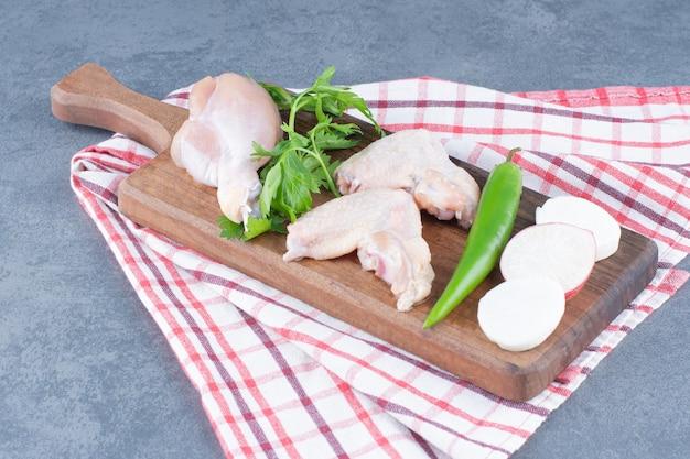 Asas de frango cru e coxa na placa de madeira.