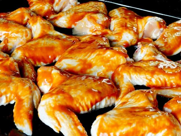 Asas de frango cru em molho vermelho quente em uma assadeira antes de assar.