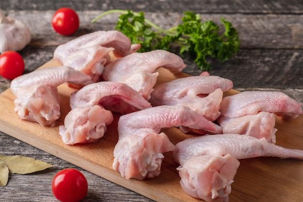 Asas de frango cru em uma tábua de madeira. fechar-se