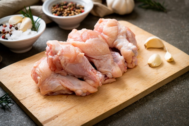 Asas de frango cru fresco (bateria ou baqueta) na placa de madeira