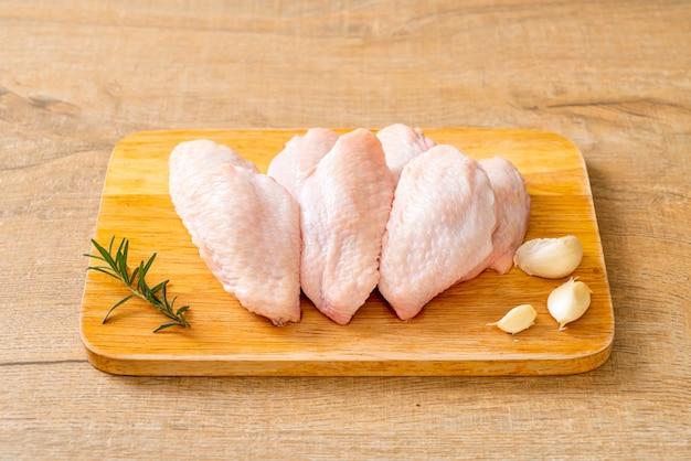 Asas de frango cru fresco médio na placa de madeira