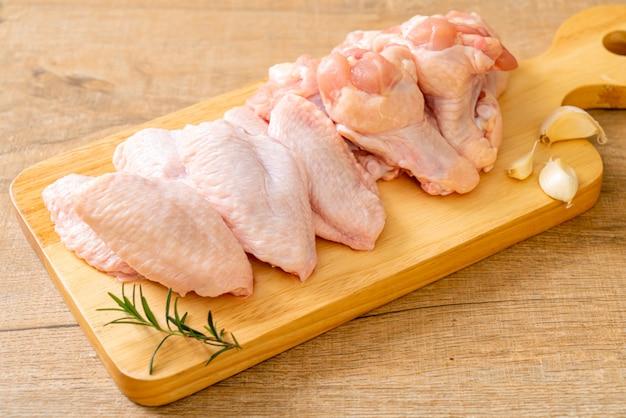 Asas de frango cru fresco na placa de madeira
