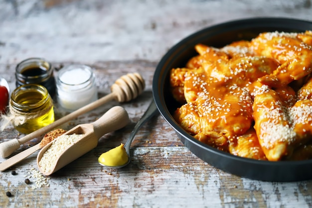 Asas de frango cru marinado em uma frigideira antes de cozinhar. cozinhar asas de frango. receita de asas de búfalo. keto paleo. pegan.