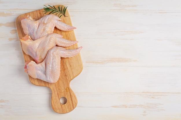 Asas de frango cru na superfície de madeira branca.