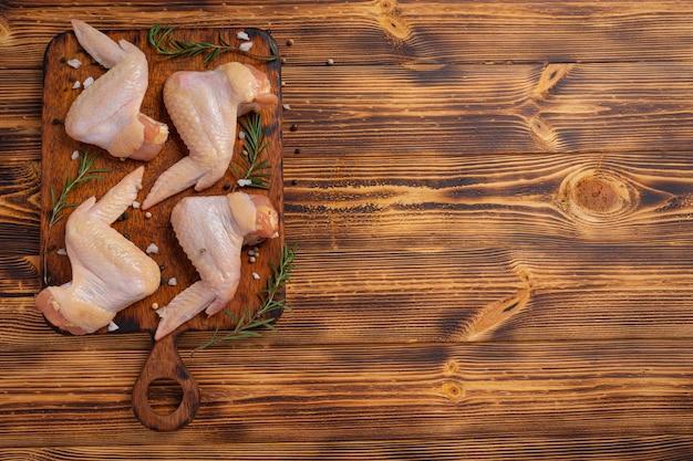 Asas de frango cru na superfície de madeira escura.