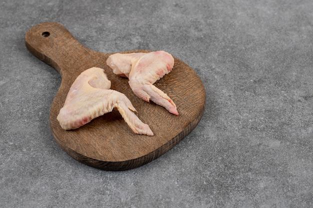 Asas de frango cru orgânico na placa de madeira.