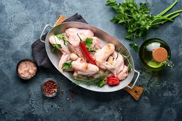 Asas de frango cruas em uma panela de metal ou tigela com especiarias e ingredientes para cozinhar