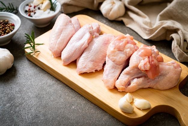 Asas de frango cruas frescas na placa de madeira