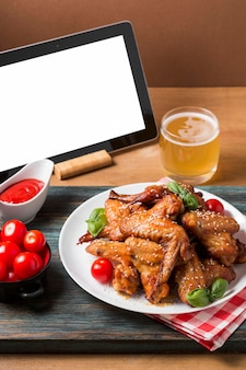 Asas de frango de ângulo alto no prato com tablet em branco
