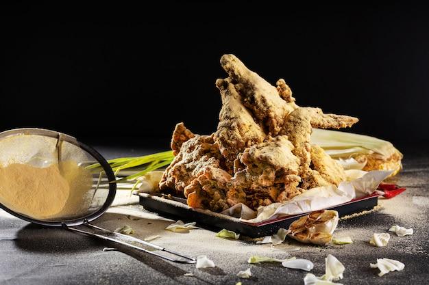 Asas de frango deliciosamente cozidas e temperadas com alho na mesa sob as luzes