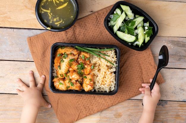 Asas de frango e arroz com cebola, mãos de crianças com colher