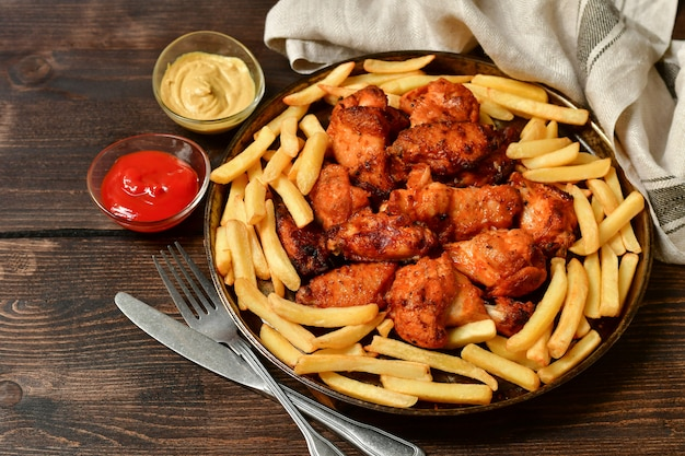 Asas de frango e batatas fritas com ketchup e mostarda.