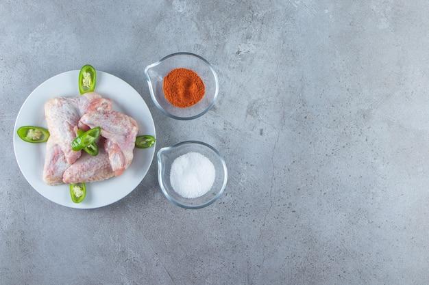 Asas de frango em um prato ao lado de tigelas de temperos e sal, no fundo de mármore.