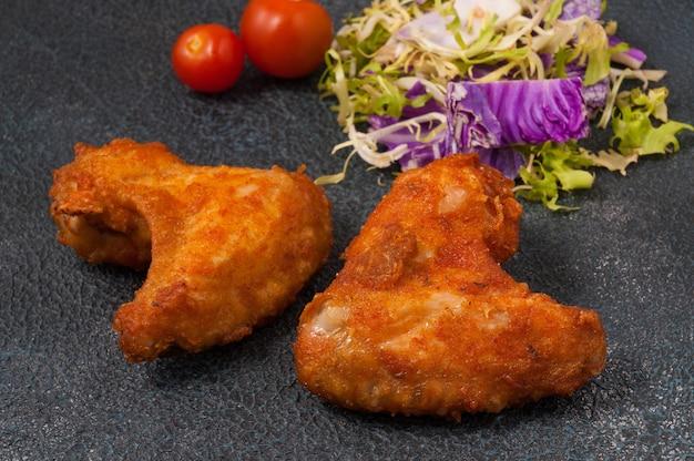 Asas de frango empanadas saborosas em um fundo escuro