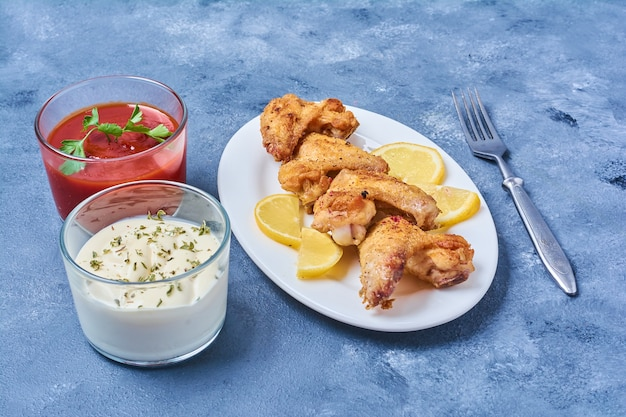 Asas de frango fritas e servidas com molhos.