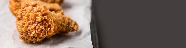 Asas de frango frito close-up com cópia-espaço