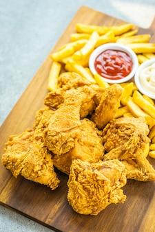 Asas de frango frito com batatas fritas e tomate