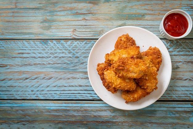 Asas de frango frito com ketchup - comida não saudável