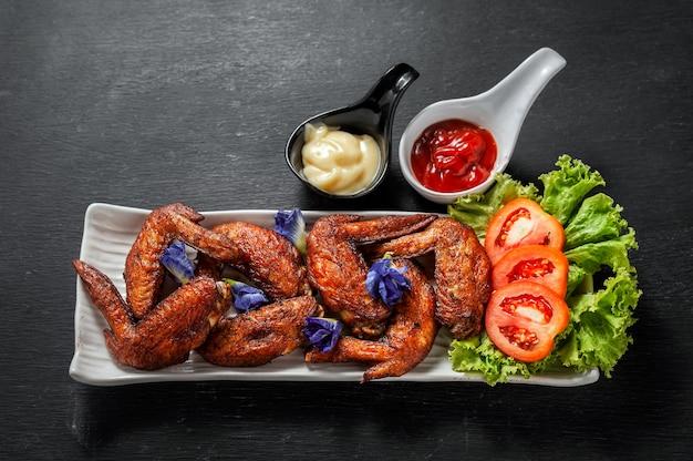 Asas de frango frito com ketchup e salada