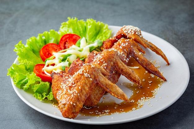 Asas de frango frito com molho de peixe e molho de peixe doce.